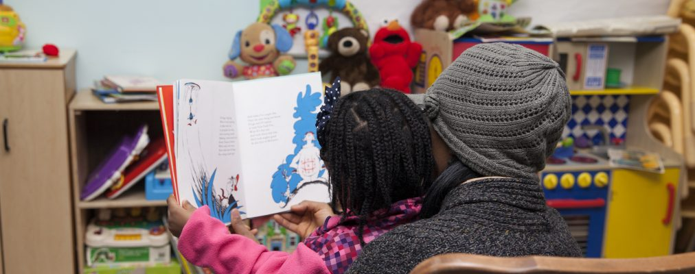 Back of mother and child's head while reading children's book