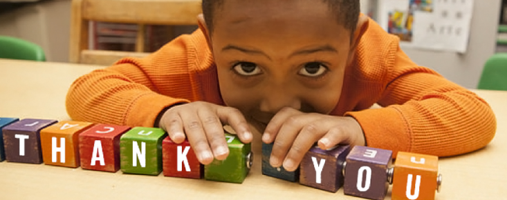 Child with blocks that spell out 'Thank You'