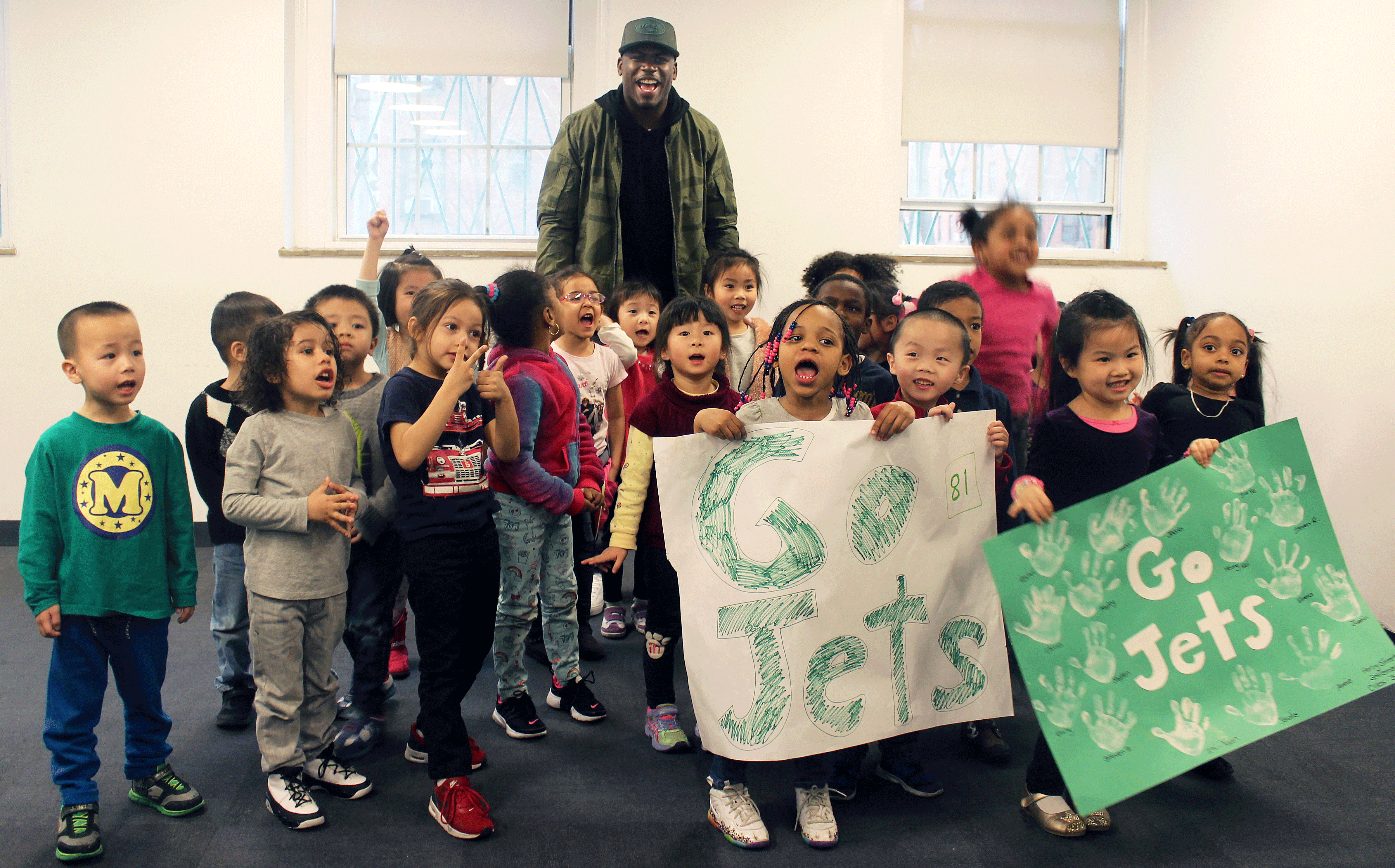 Football player Quincy Enunwa with smiling children from Early Childhood Education