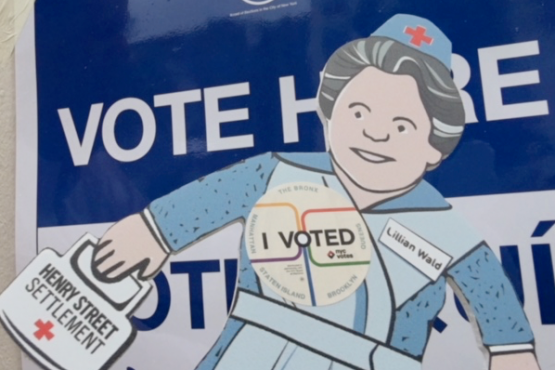 Flat Lillian, a paper doll representation of Henry Street Settlement founder Lillian Wald, outside of a polling location with 'I Voted' button