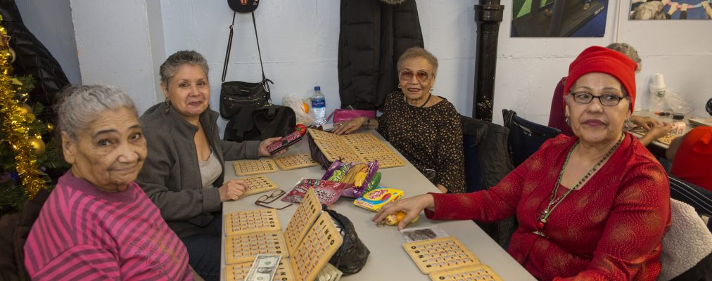 Seniors at senior center smile for camera while playing Bingo