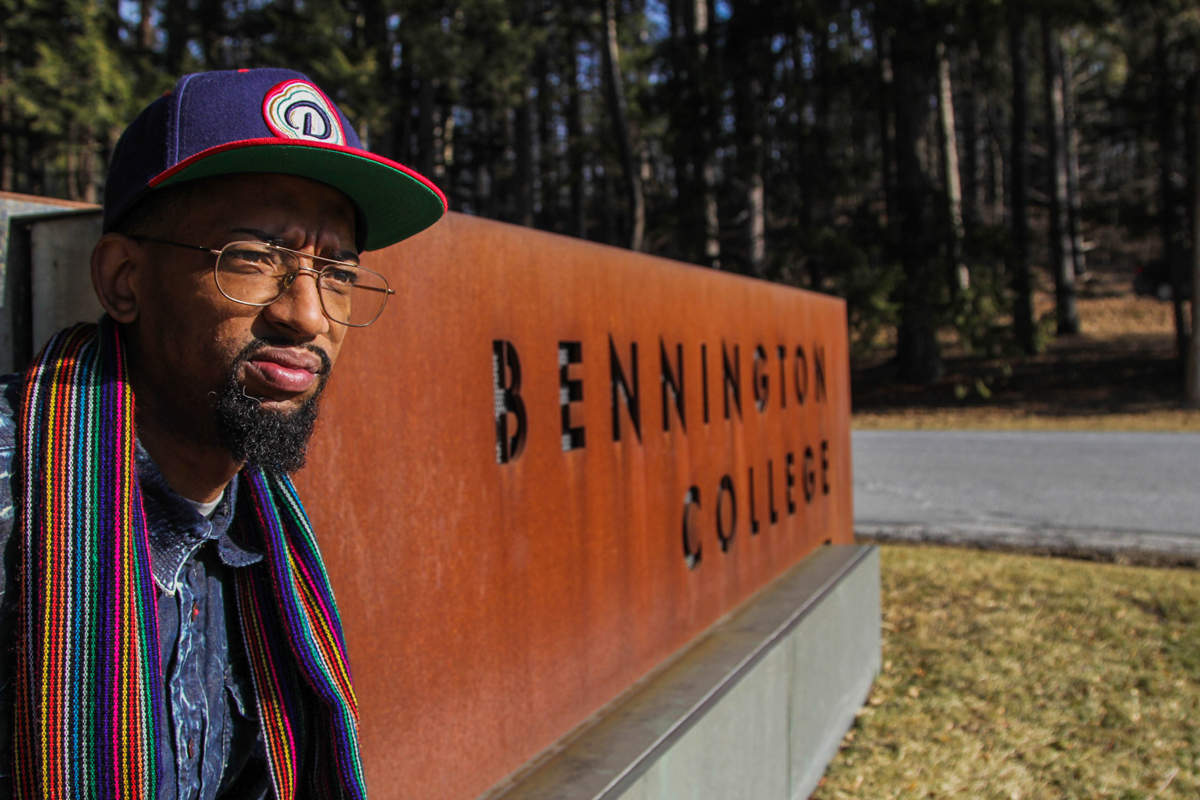 Photo of man in front of Bennington College sign
