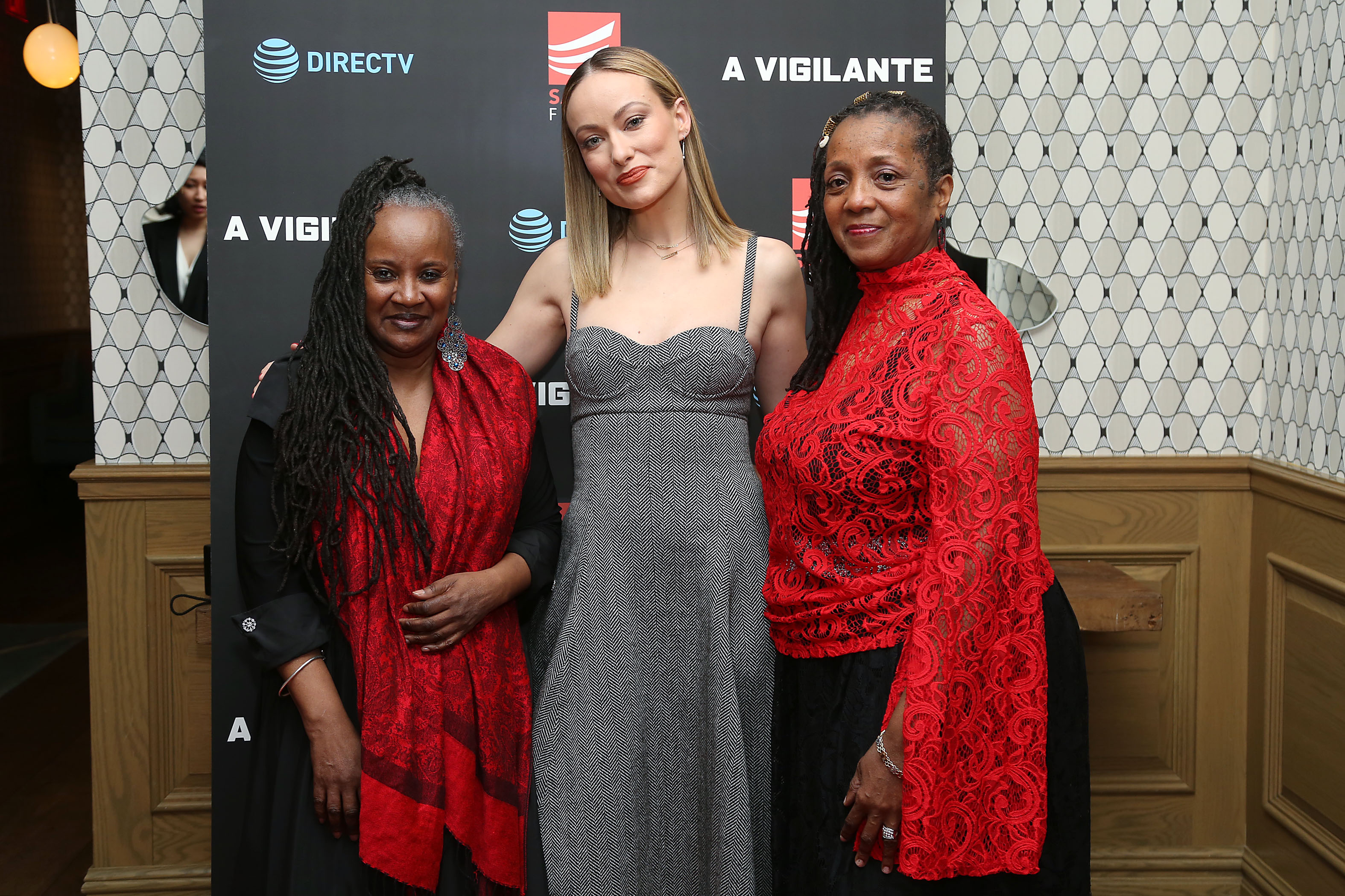 Beverly Atkinson (Assistant Program Director, Domestic Violence Program, Henry Street Settlement), Olivia Wilde, Theather Huggins (Housing Specialist, Domestic Violence Program, Henry Street Settlement) in front of step and repeat at event