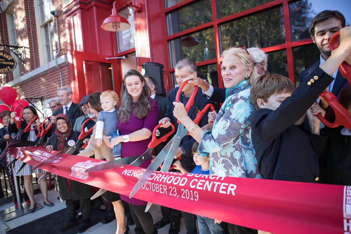 Large multigenerational group at ribbon cutting of new building
