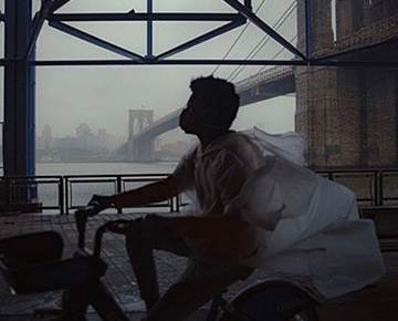 Person in a mask and poncho rides a bike under the Brooklyn Bridge