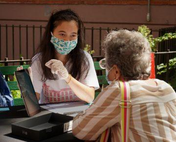Young volunteer helps senior set up her iPad
