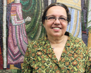 Woman in green and brown shirt stands in front of a colorful mosaic wall.