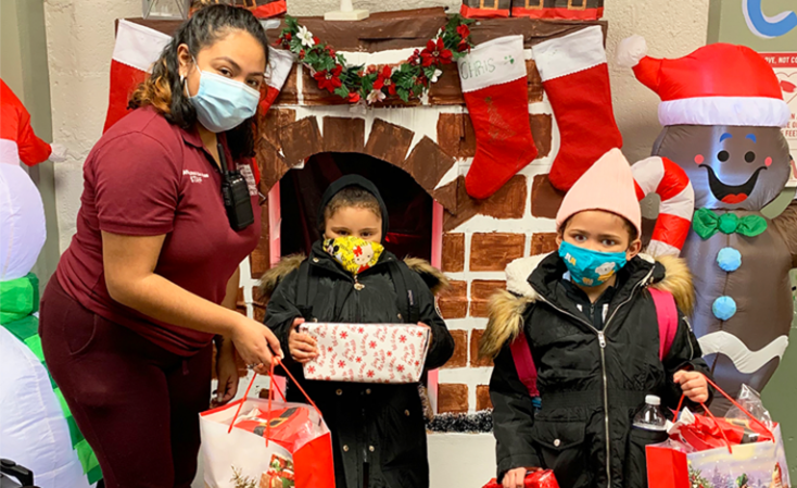Masked adult & two masked children with gifts, standing in front of a cardboard fireplace decorated for the holidays.