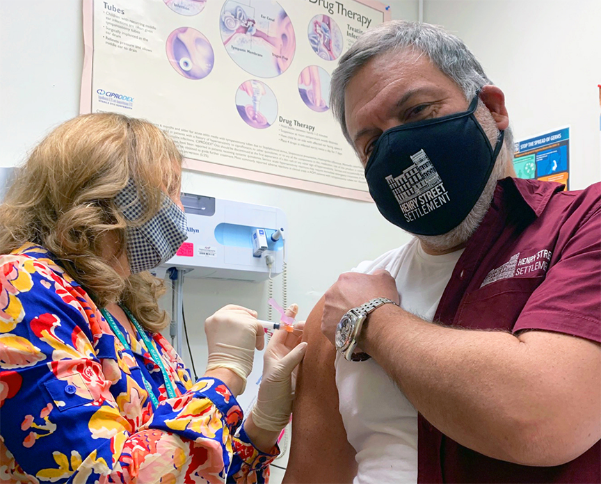 A woman wearing a mask and a blue, yellow, and red patterned shirt gives a COVID-19 vaccination to Henry Street Settlement President & CEO David Garza, who wears a maroon Henry Street Settlement shirt and black Henry Street Settlement mask