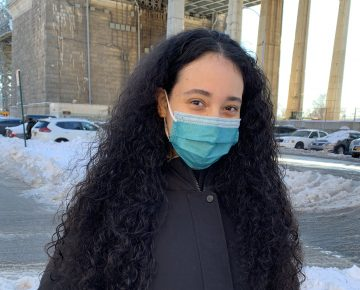 Woman smiles at camera in face mask
