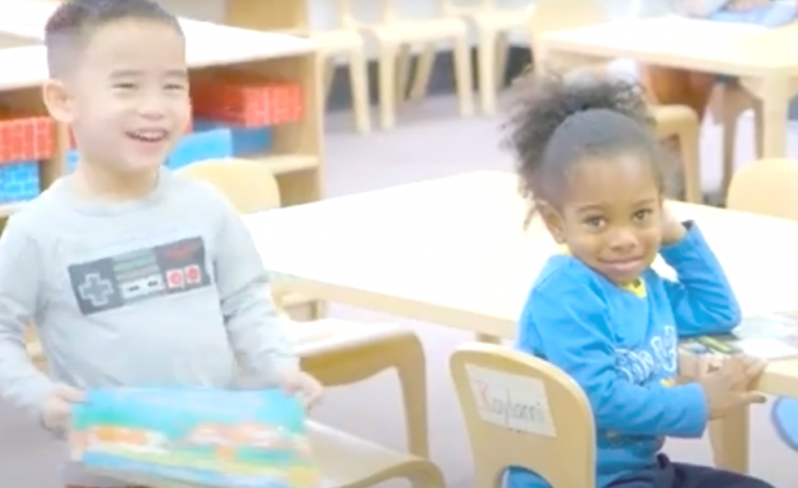 Young children from our Early Childhood Education smile at camera
